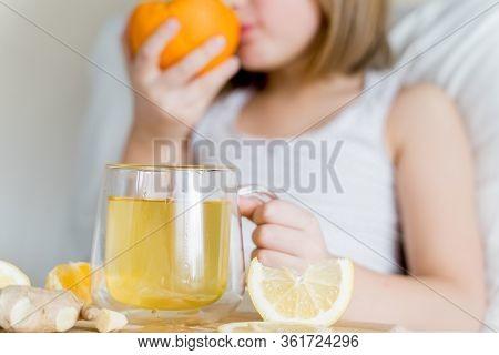 Sick Girl In Bed Tastes Half Of Orange.cup Of Antipyretic Drugs. Colds,flu.tea With Citrus Vitamin C