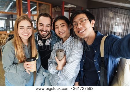 Photo of multinational cheerful students laughing while taking selfie photo in classroom