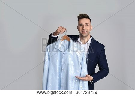 Man Holding Hanger With Shirt In Plastic Bag On Light Grey Background. Dry-cleaning Service