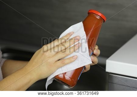 Covid-19 Pandemic Coronavirus Woman Disinfect Bottle Of Tomato Puree With Wet Wipes Cleaning Against