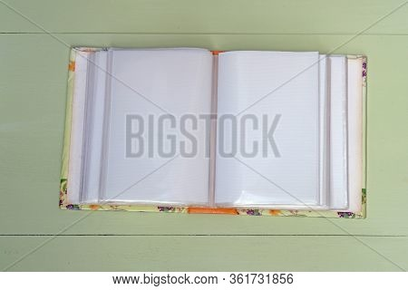 Old Empty Photo Album On Wooden Background. White Sheets With A Film For Photos. Old Photo Album Ope