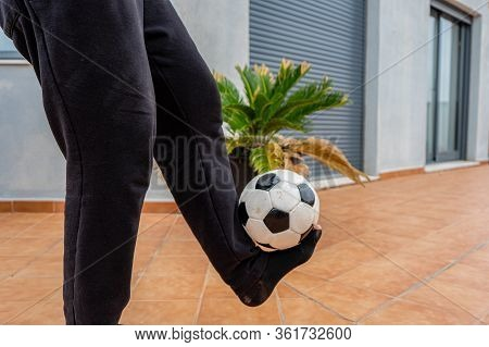 Man With Leaky Black Sock Playing With A Soccer Ball On The Terrace Of His House. Game Concept
