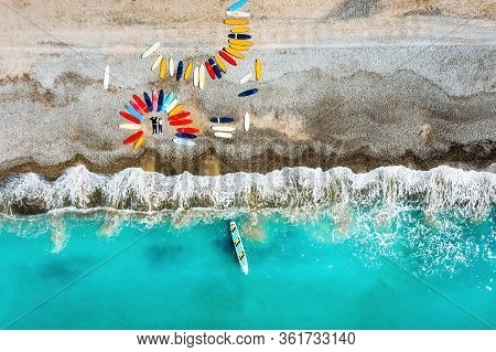 A Beautiful Couple Is Lying On The Beach Of France Next To Surfboards, Shooting From A Quadcopter, A