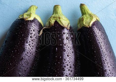 Dark Purple Eggplants Sprinkled With Water. 3 Eggplants Close-up Above View. Freshly Harvested Veget