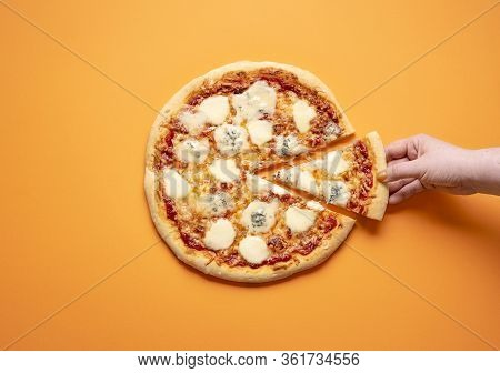 Quattro Formaggi Pizza And A Woman Hand Taking One Pizza Slice, On An Orange Seamless Background. Fl
