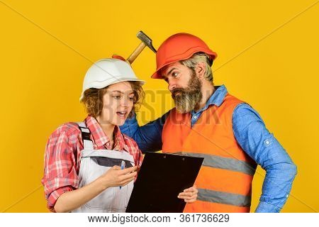 Renovation Concept. Couple Planning Changes Renovation Apartment. Woman And Man Wear Safety Hard Hat