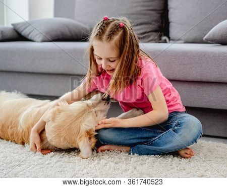 Cute little girl playing with lovely dog on floor at home