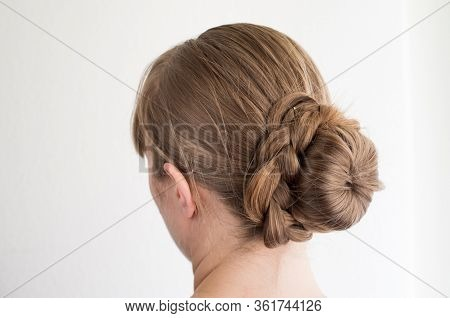 Caucasian Young Woman With Her Hair In A French Bun With Frizzy Loose Hairs Seen From Behind Not Rec