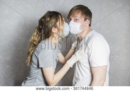 A Girl In A Medical Mask Kisses. A Couple In Love, A Man And A Woman Kiss Each Other In A Protective