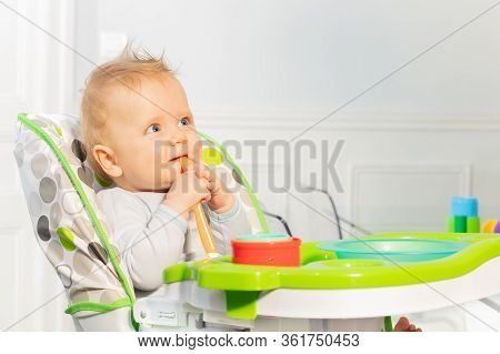 Happy Little Toddler Baby Boy Sit In Highchair Holding Plastic Spoon In Mouse With Thoughtful Look