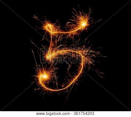 number five written with a sparkler on a black background