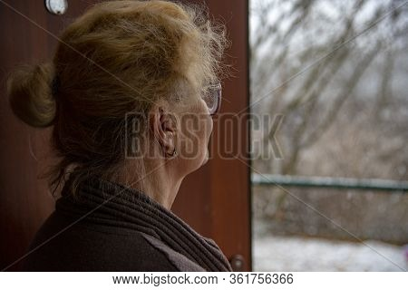 An Elderly Woman Stands In The Doorway And Looks Out At The Street.