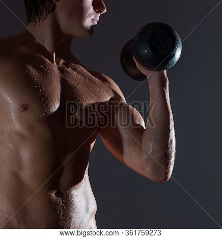 Young bodybuilder with naturally looking and wet body (bady has hairs and birthmarks) hold dumbbell