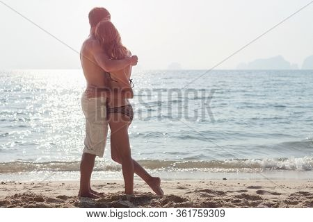 Young happy couple stands on the tropical beach. Man and woman hugging and enjoying pleasant weather on the beach.