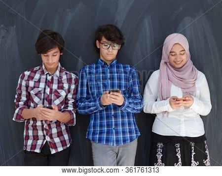 arab teenagers group using smart phones for social media networking against black chalkboard