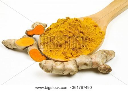 Turmeric Powder In Wooden Spoons And Turmeric Roots Isolated On A White Background, Used As A Tonic