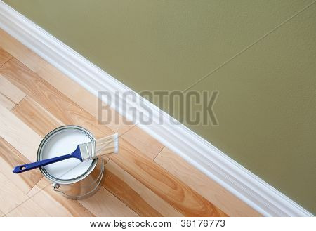 Newly opened can of white paint and paintbrush on wooden floor. poster