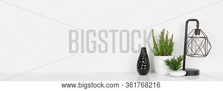 Home Decor On A Shelf. Industrial Style Lamp, Vase And Plants. White Shelf And Wall. Banner With Cop