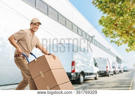 Delivery man pushing a hand truck with boxes outside a warehouse