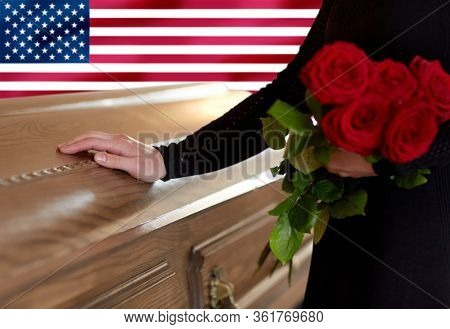 people and mourning concept - woman with red roses and coffin at funeral over flag of america on background
