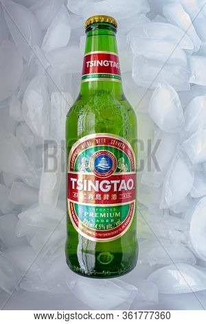 Calgary, Alberta, Canada. April 17, 2020. A Tsingtao Beer Bottle On A Bed Of Ice.