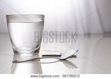 Ors Or Oral Rehydration Salt With Glass Of Water, Sachet And Spoon On Table Against Window Light
