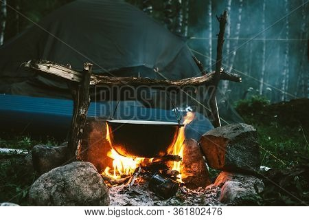 Kettle On Fire Near Tent In Forest At Night. Beautiful Campfire In Tourist Camp Into Wild. Survival