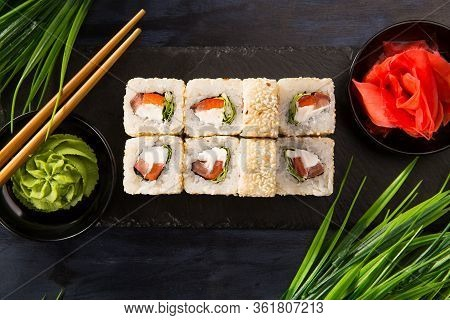 Set Of Sushi Rolls With Wasabi And Ginger On A Black Background. Japanese Oriental Cuisine