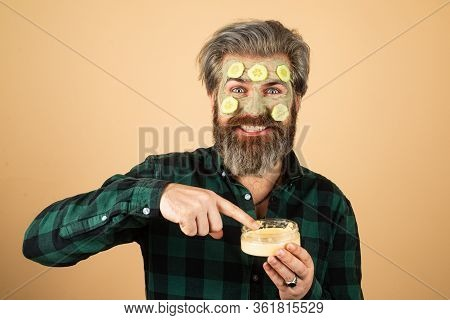 Procedure For Applying A Mask From Clay To The Face Of Funny Man. Home Spa. Men Holding Pieces Of Cu