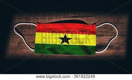 Ghana National Flag At Medical, Surgical, Protection Mask On Black Wooden Background. Coronavirus Co