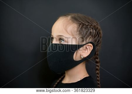 Girl With Red Eyes And Black A Medical Mask On A Black Background, Copy Space. Concept Of People Who
