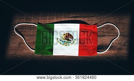 Mexico National Flag At Medical, Surgical, Protection Mask On Black Wooden Background. Coronavirus C