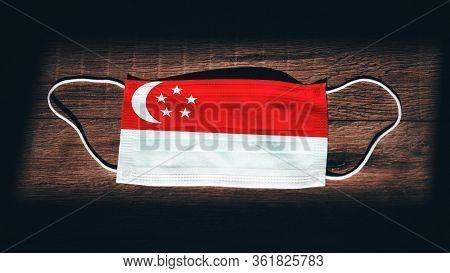 Singapore National Flag At Medical, Surgical, Protection Mask On Black Wooden Background. Coronaviru