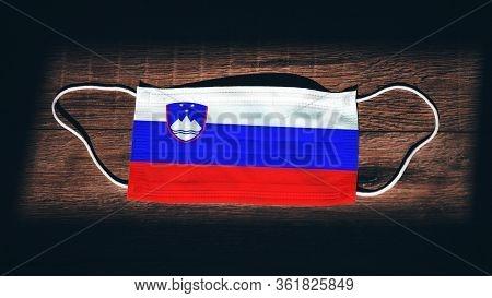Slovenia National Flag At Medical, Surgical, Protection Mask On Black Wooden Background. Coronavirus