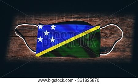 Solomon Islands National Flag At Medical, Surgical, Protection Mask On Black Wooden Background. Coro