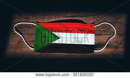Sudan National Flag At Medical, Surgical, Protection Mask On Black Wooden Background. Coronavirus Co