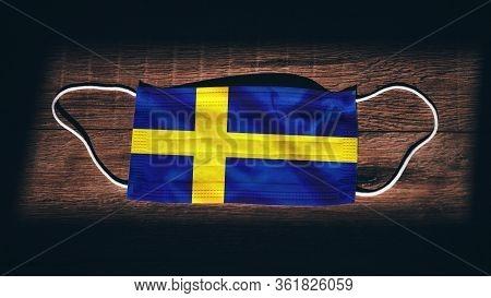 Sweden National Flag At Medical, Surgical, Protection Mask On Black Wooden Background. Coronavirus C