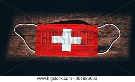 Switzerland National Flag At Medical, Surgical, Protection Mask On Black Wooden Background. Coronavi