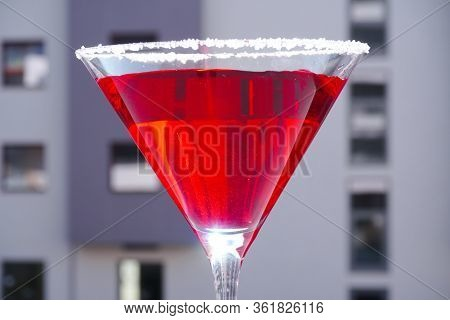 Red Cocktail In A Martini Glass On A Gray Background. Red Liquid In A Glass. Glass Beaker