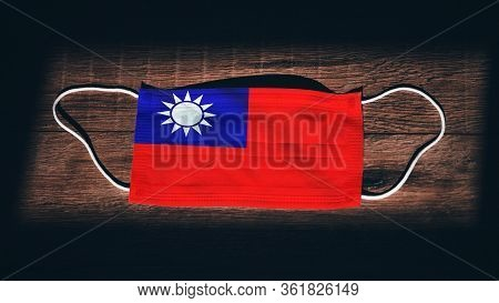 Taiwan National Flag At Medical, Surgical, Protection Mask On Black Wooden Background. Coronavirus C