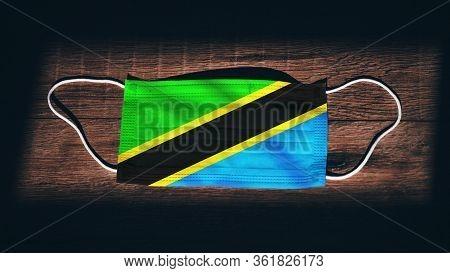 Tanzania National Flag At Medical, Surgical, Protection Mask On Black Wooden Background. Coronavirus