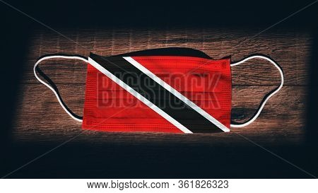 Trinidad And Tobago National Flag At Medical, Surgical, Protection Mask On Black Wooden Background.