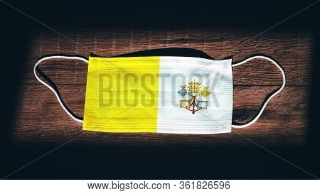 Vatican National Flag At Medical, Surgical, Protection Mask On Black Wooden Background. Coronavirus