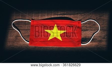 Vietnam National Flag At Medical, Surgical, Protection Mask On Black Wooden Background. Coronavirus