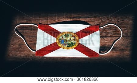 Florida Flag. Coronavirus Covid 19 In U.s. State. Medical Mask Isolate On A Black Background. Face A
