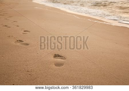 Natural Background For Text And Sand And Sea Waves. Footprints In The Sand From The Legs Go Into The