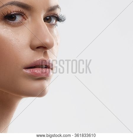 Tear On The Cheek Of A Beautiful Young Woman. Emotions And Sadness. Portrait Of An Attractive Sad Gi