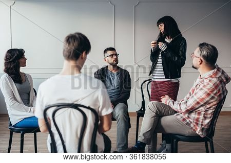 Sad Teenager Stands In Front Of A Group Of People Of Different Ages During A Therapy Group Meeting A