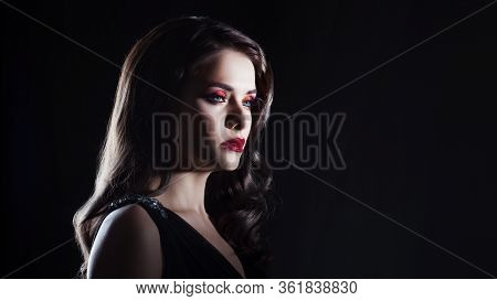 Portrait Of A Young Luxurious Woman In A Low Key. Bright Makeup With Scarlet Lipstick, Hairstyle Wit