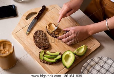 Woman Making Avocado Peanut Butter Toast For A Healthy Breakfast At Home